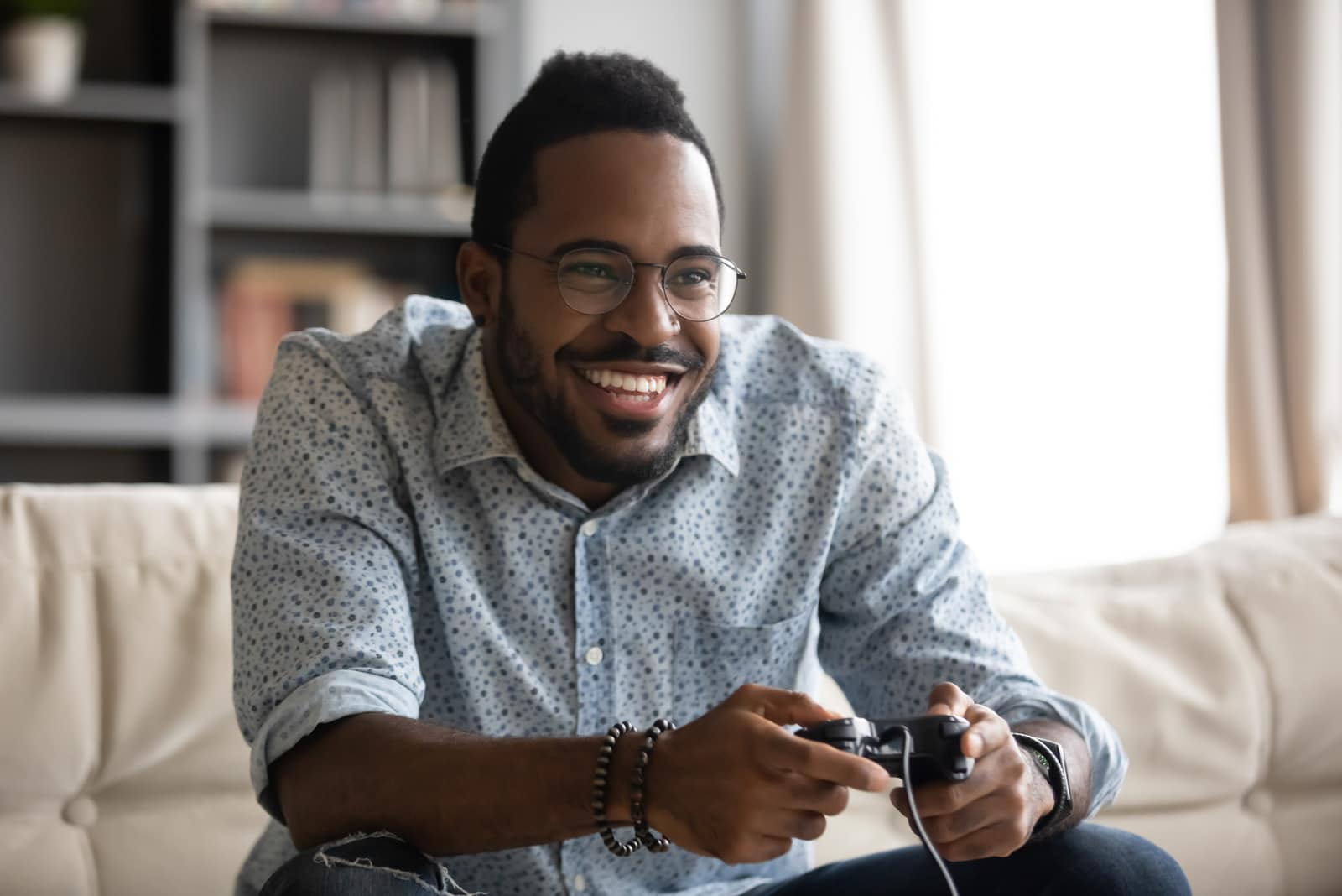smiling black man plays play station