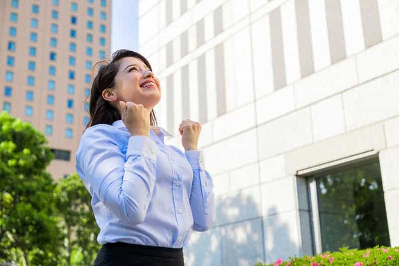 smiling business woman standing outside