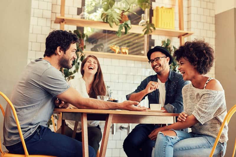 smiling friends having positive conversation at cafe