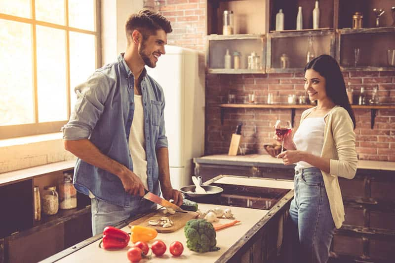 smiling man cuts mushrooms with a knife in kitchen and looking at woman