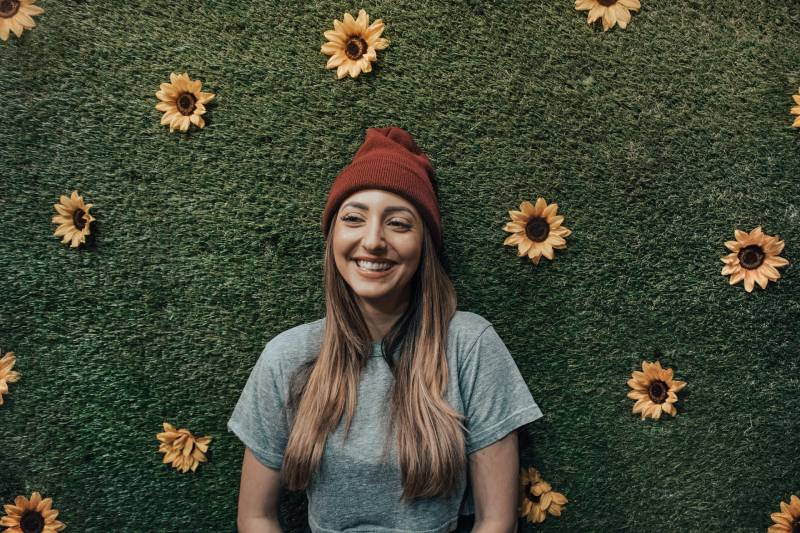 smiling woman leaning on flower wall