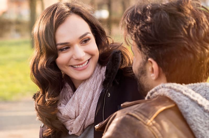 smiling woman looking at her man outside