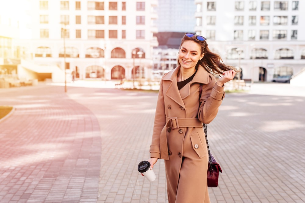 the woman is standing in a brown coat