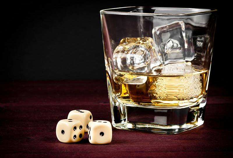 three dices next to glass with ice and whiskey