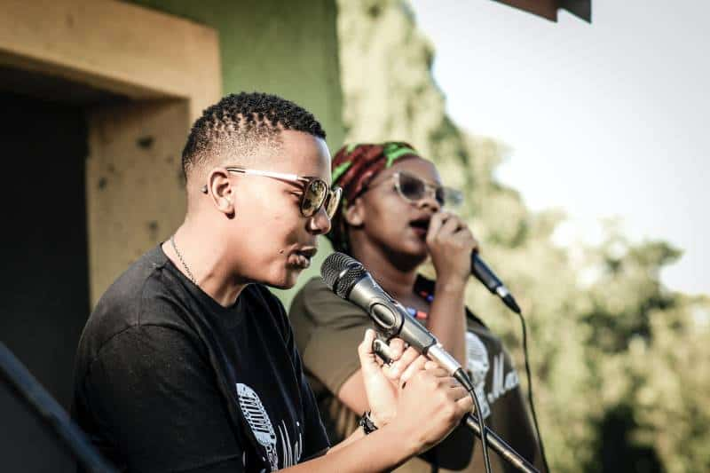 two people holding microphones and singing