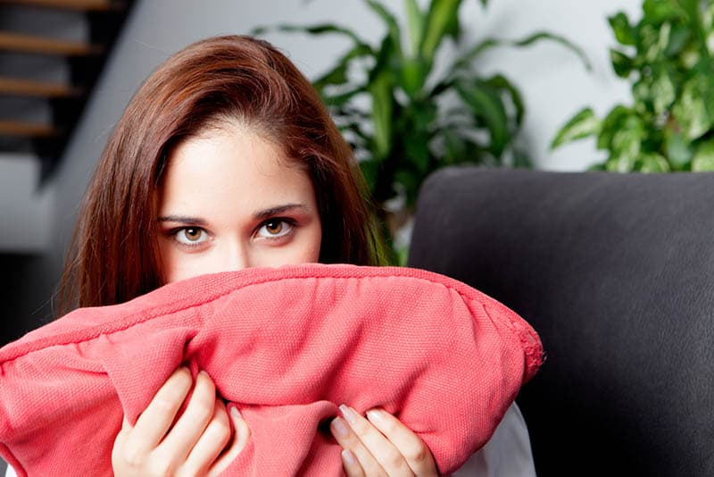 woman covered her mouth with pillow