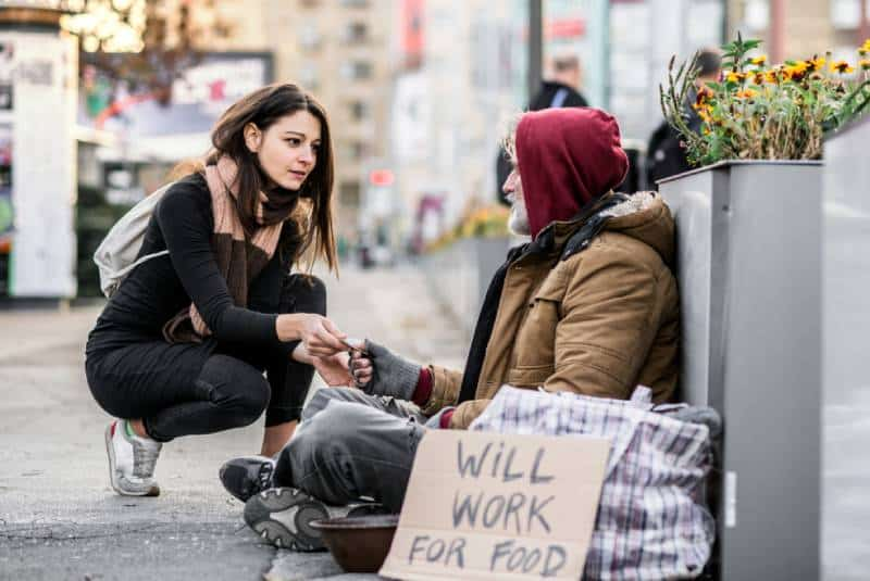 woman giving money to homeless man