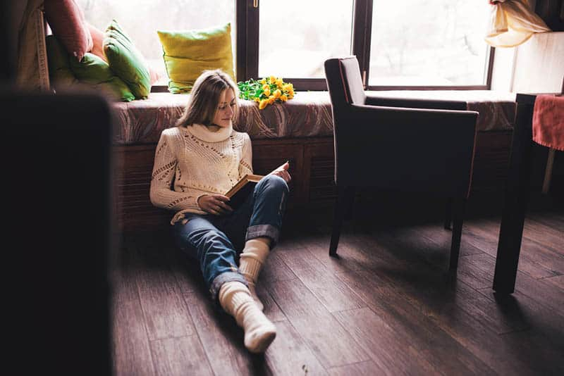 woman reading book while sitting on floor