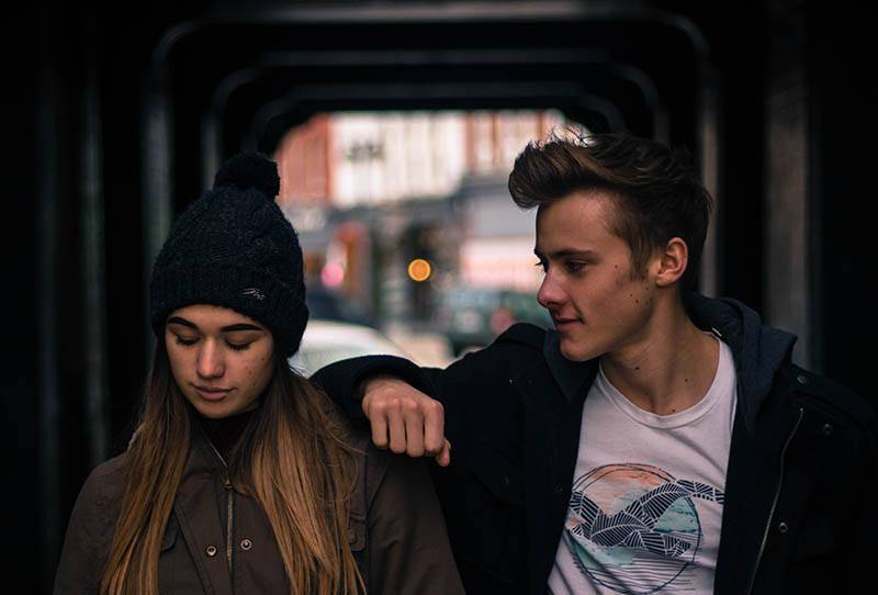 young man puts hand on girl shoulder outside