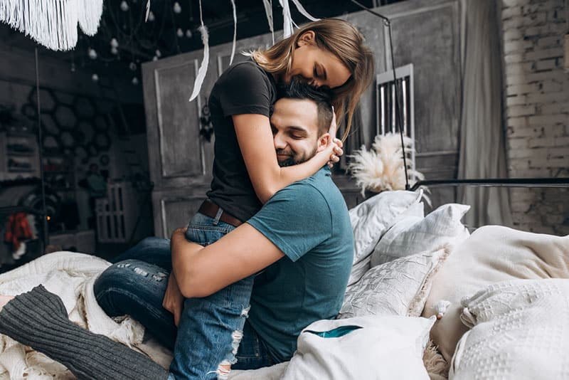 young smiling couple hugging on bed
