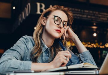 thoughtful woman wearing glasses at cafe
