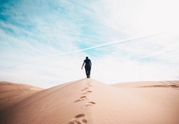 man walking on sands during daytime