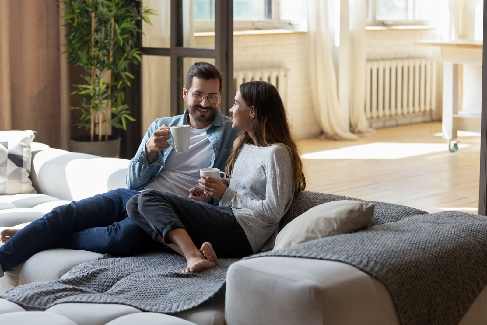 a man and a woman sit on the couch and drink coffee
