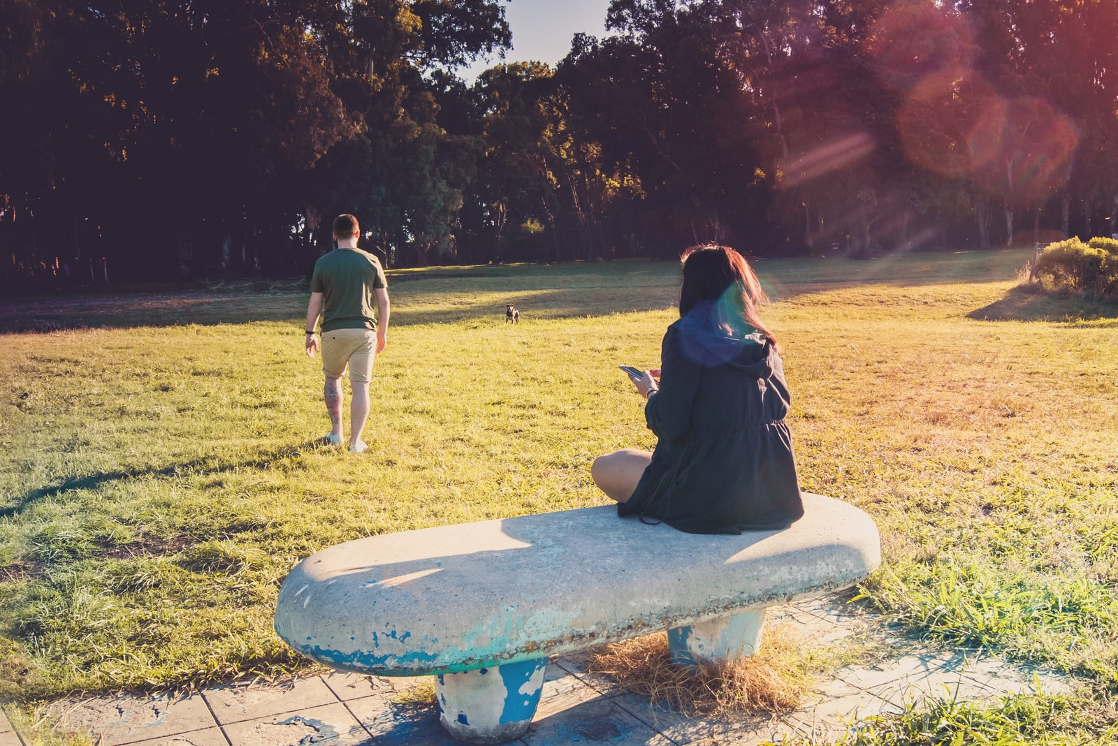 a man walks away from a woman sitting on a concrete bench in a park