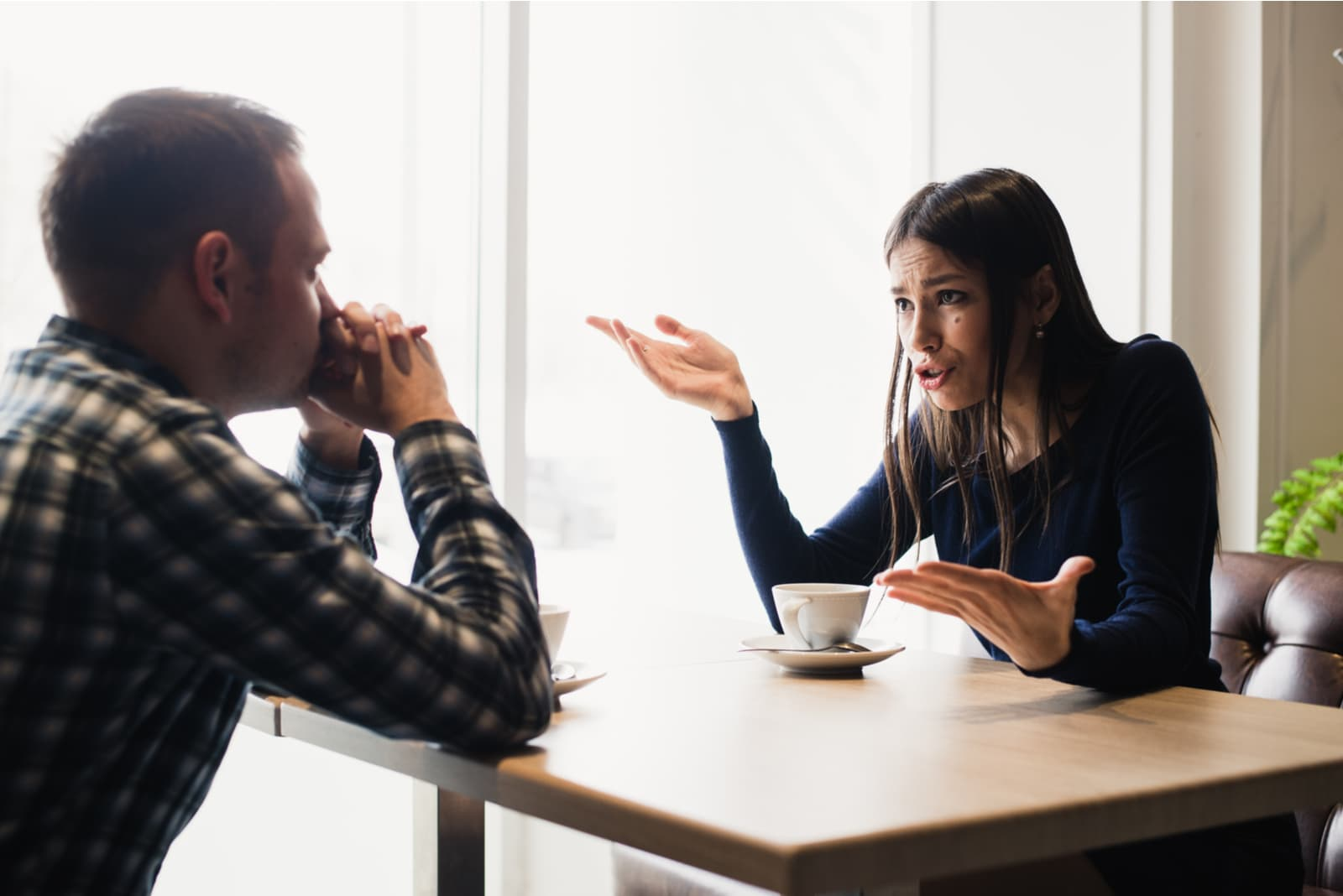 angry woman talking to man at cafe
