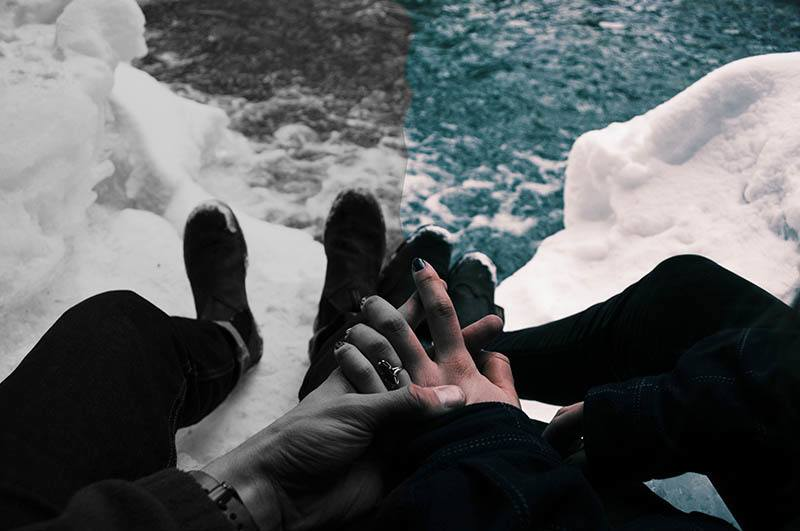 close up photo of man holds woman hands while sitting on snow rock
