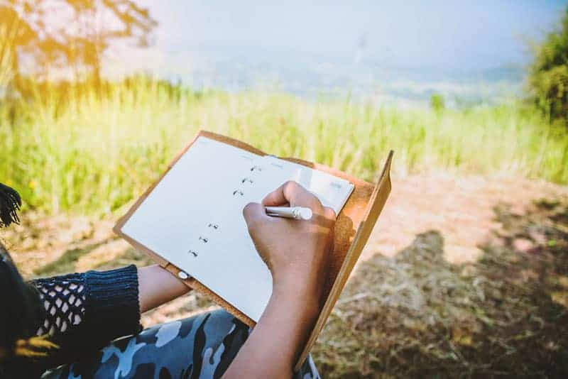 close up photo of man writing on notebook