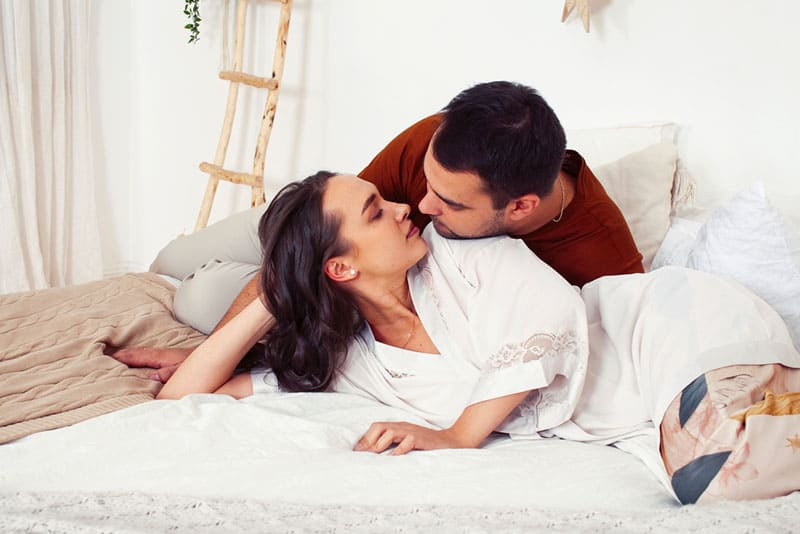 couple kissing in bedroom on the bed
