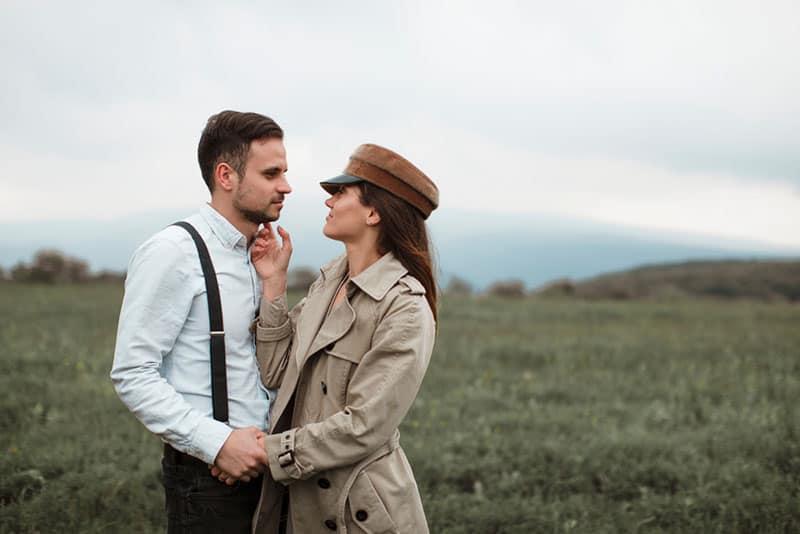 couple standing on grass field