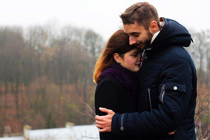 lovely couple hugging in nature beside water
