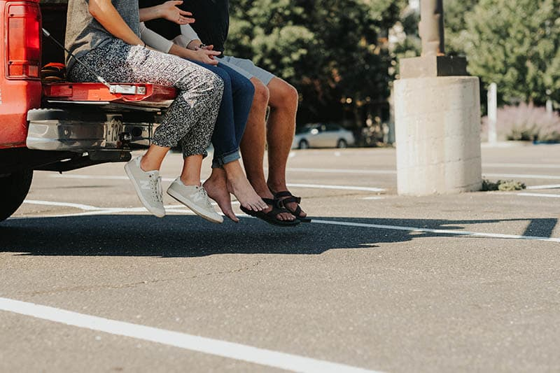 man and woman sitting at the trunk of car