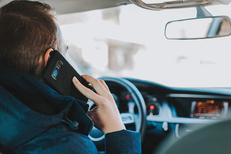 man speaking on his phone while driving car