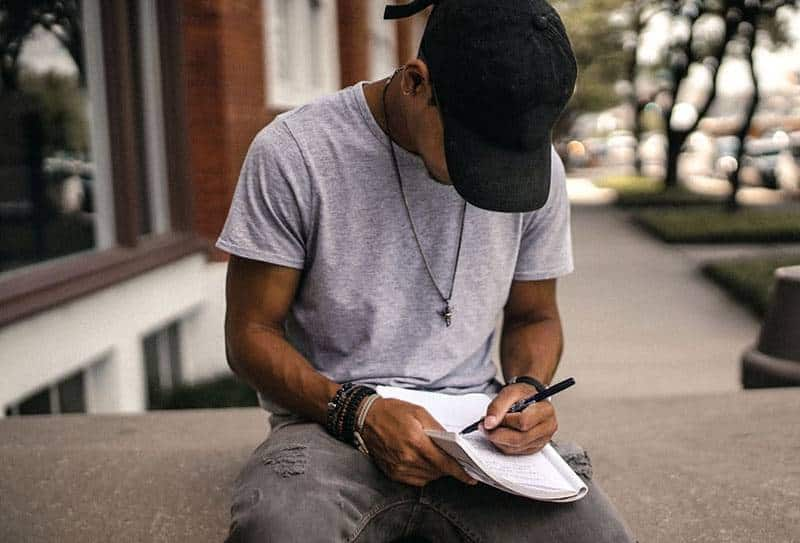 man with black hat writing on paper