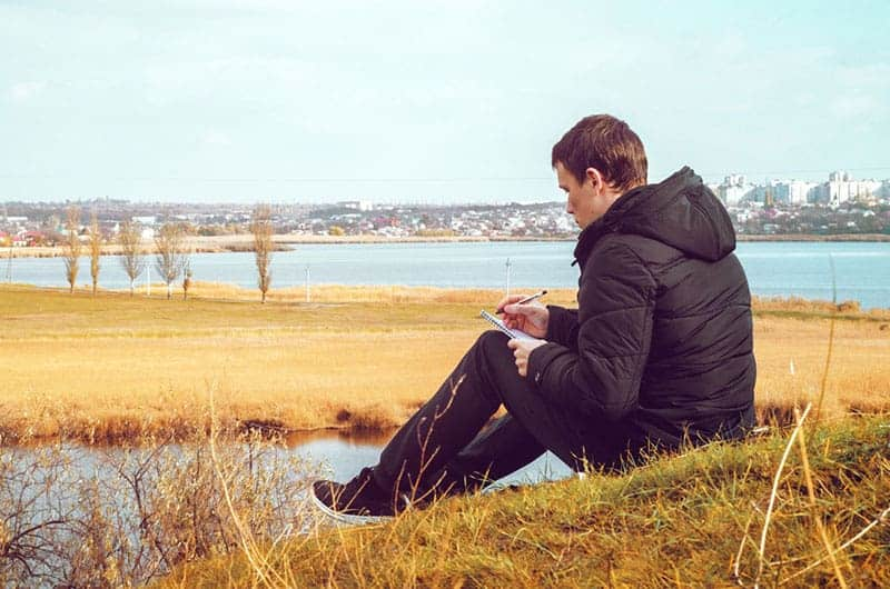 man writing on paper beside water