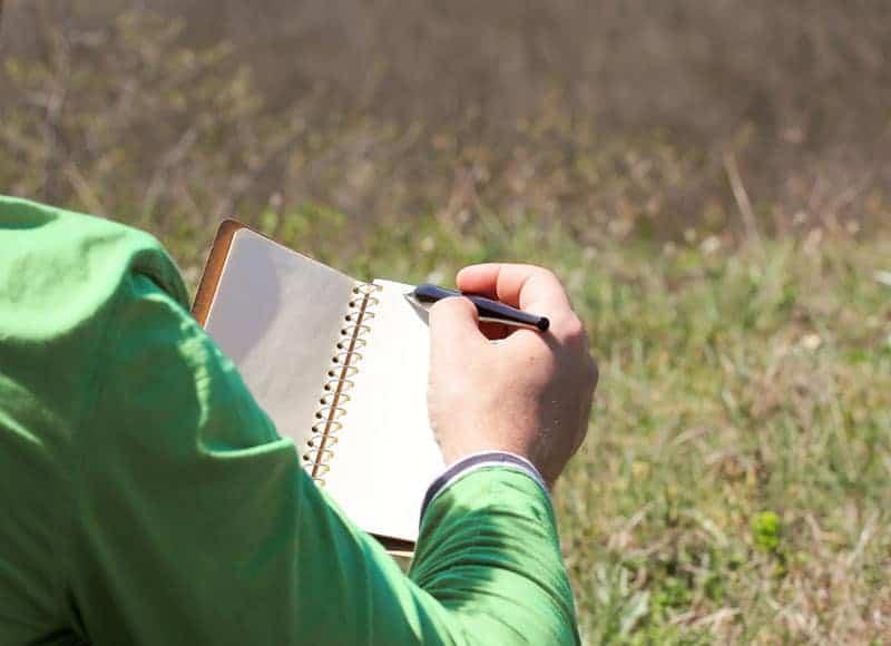 man writing on paper in field