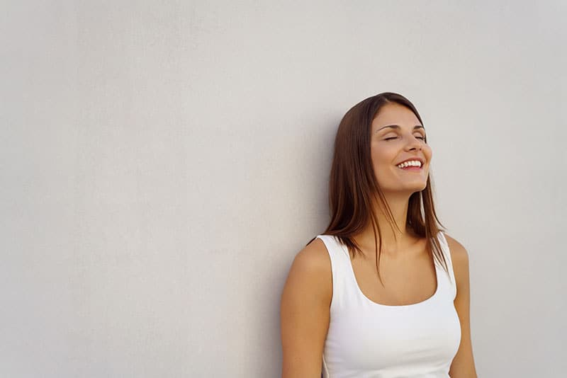 relaxed woman with closed eyes leaning on wall