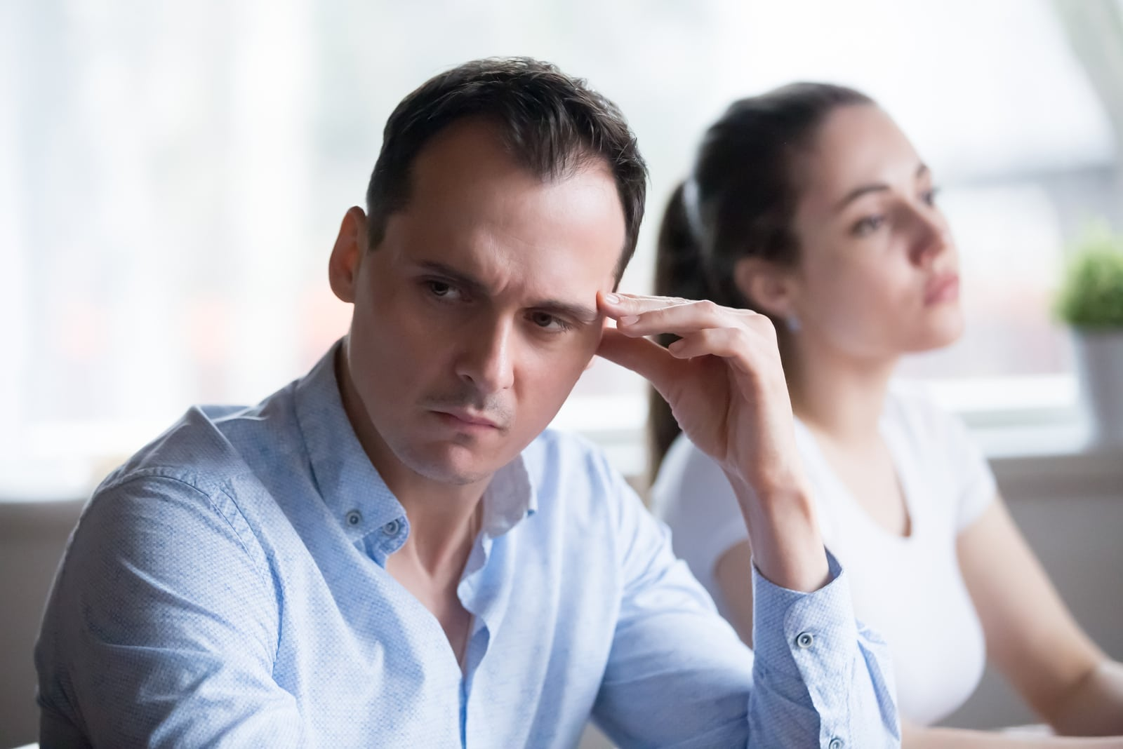 serious man looking away from woman