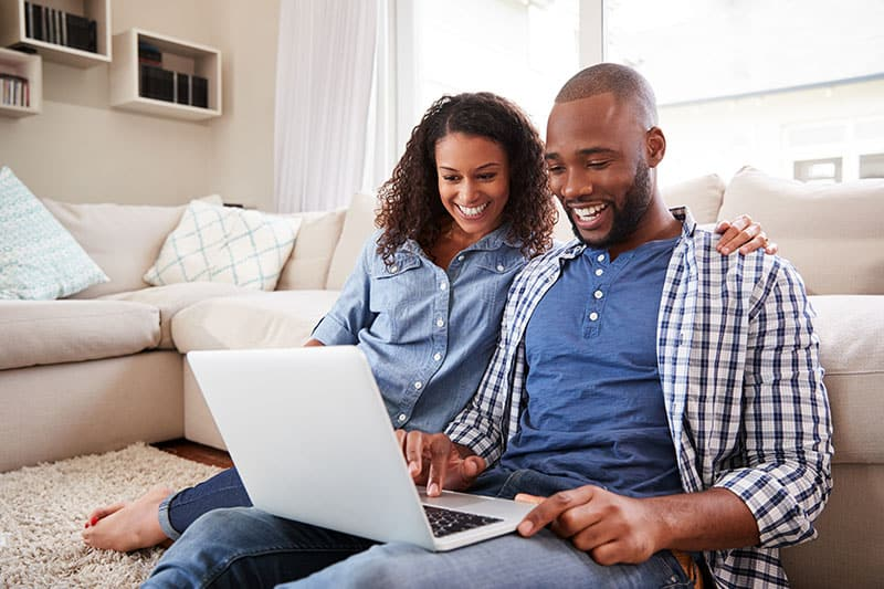 Young black couple using laptop sitting on the floor at home