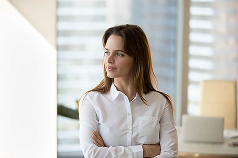 Thoughtful successful motivated businesswoman looking away dreaming of future in office, confident millennial female boss