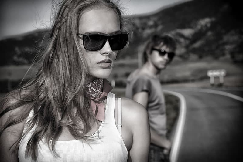 Couple of modern young people posing on a road