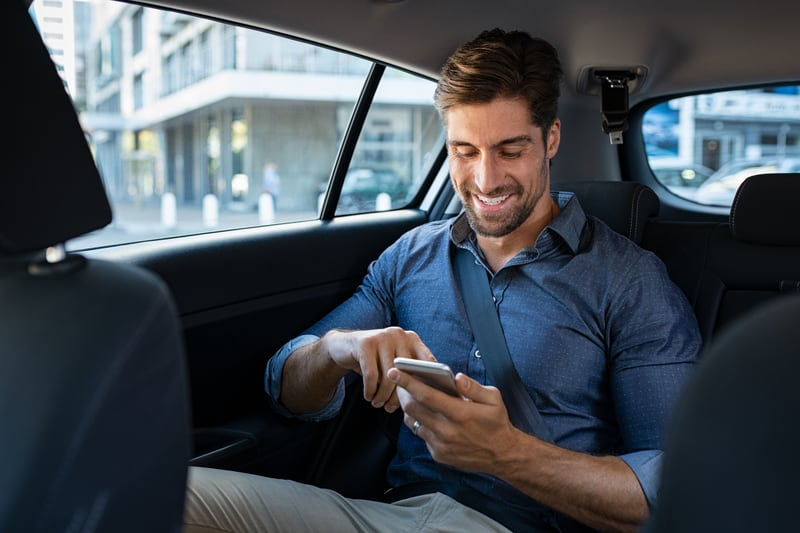 guy texting while he is in taxi