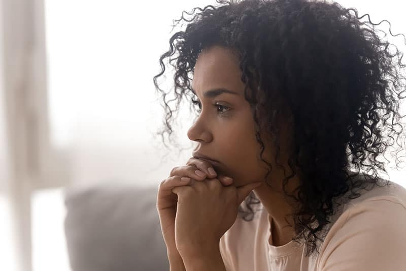 Close up side profile view of pensive young african American woman thinking of relationships problems