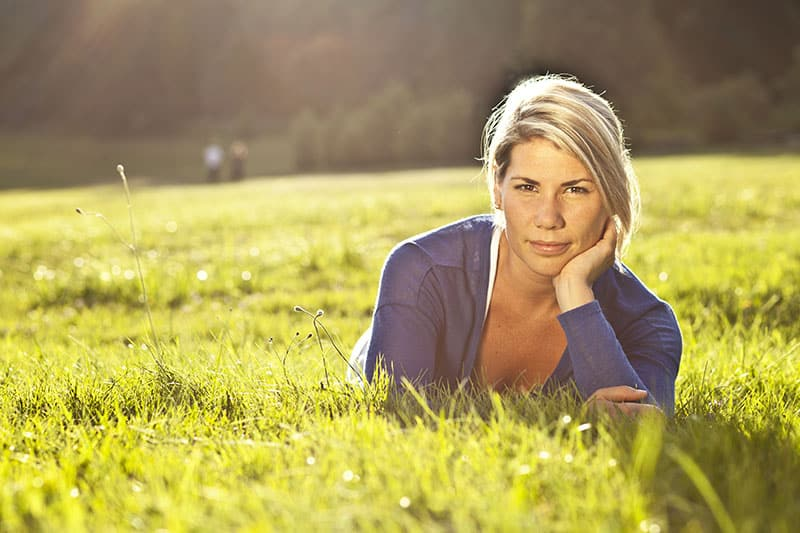 Portrait Of A Blond Woman Relaxing At The Park