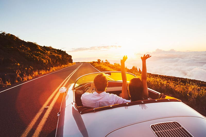Happy Couple Driving on Country Road into the Sunset
