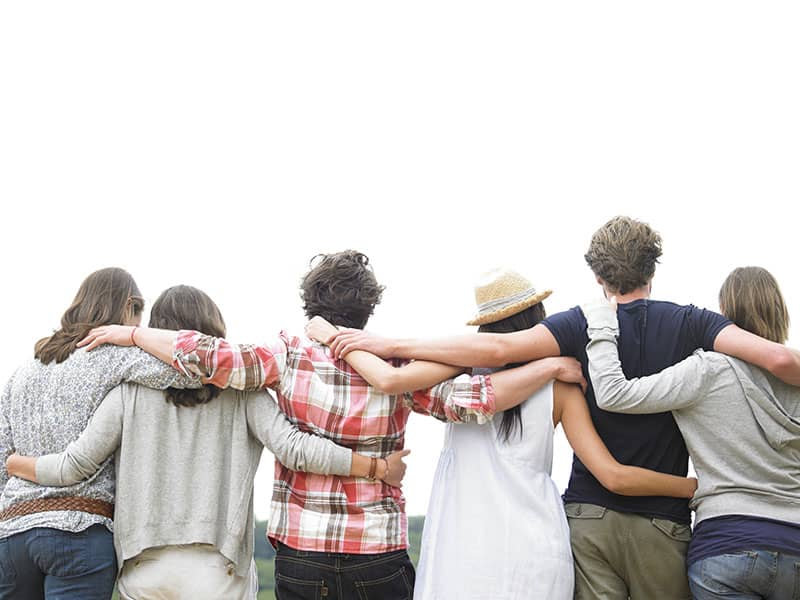 Rear view of group of friends hugging. Horizontal