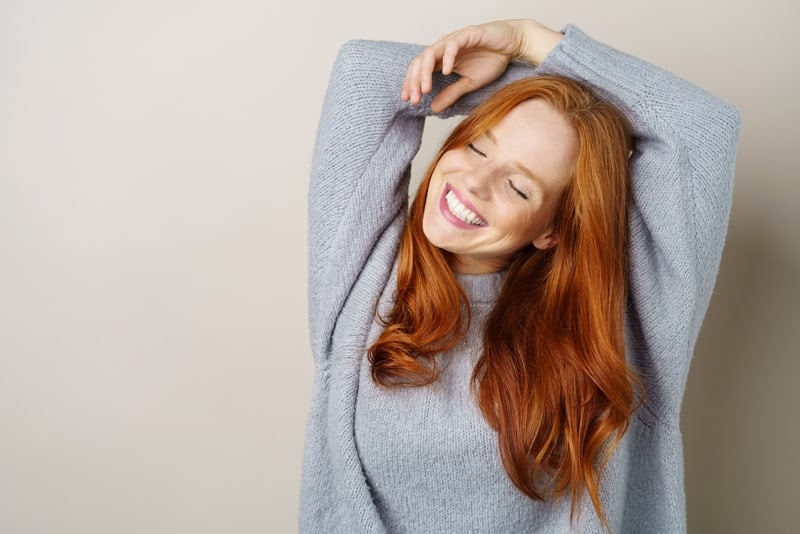 Happy carefree young redhead woman with a cute grin