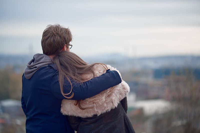 Couple hugging and looking at the horizon at the autumn