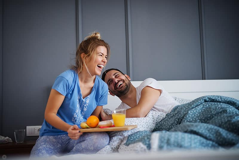 Beautiful happy young romantic girl brings breakfast to her husband in the bed