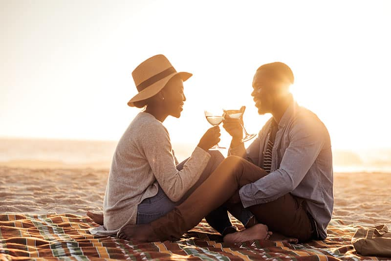 Romantic young African couple toasting each other with wine while sitting together