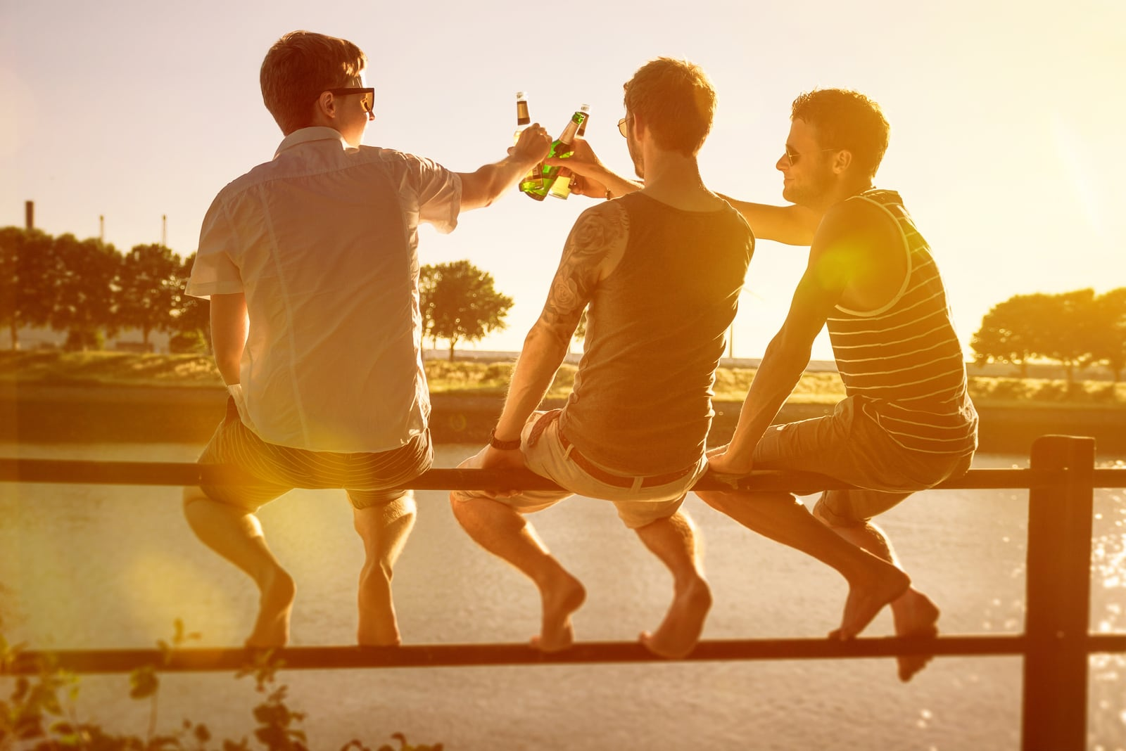 three friends sit on the fence and drink beer