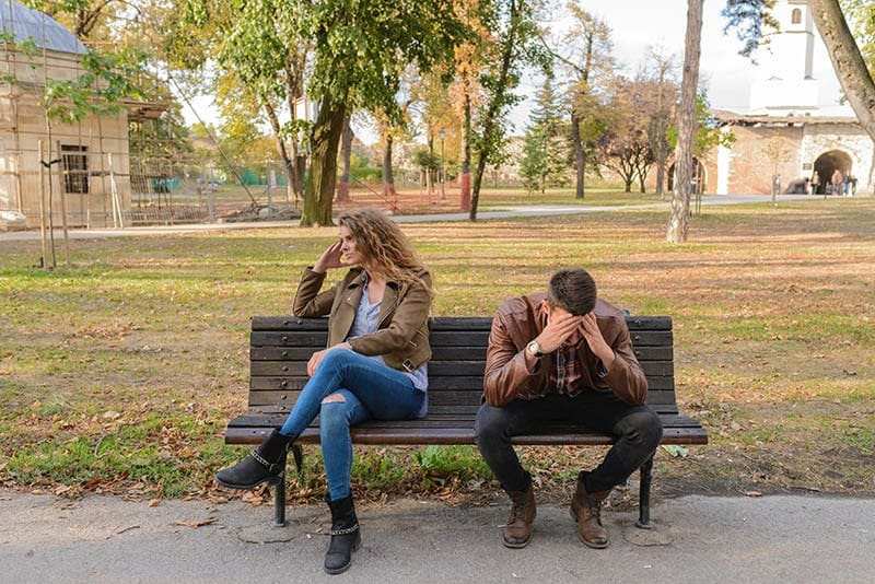 upset couple sitting at park bench