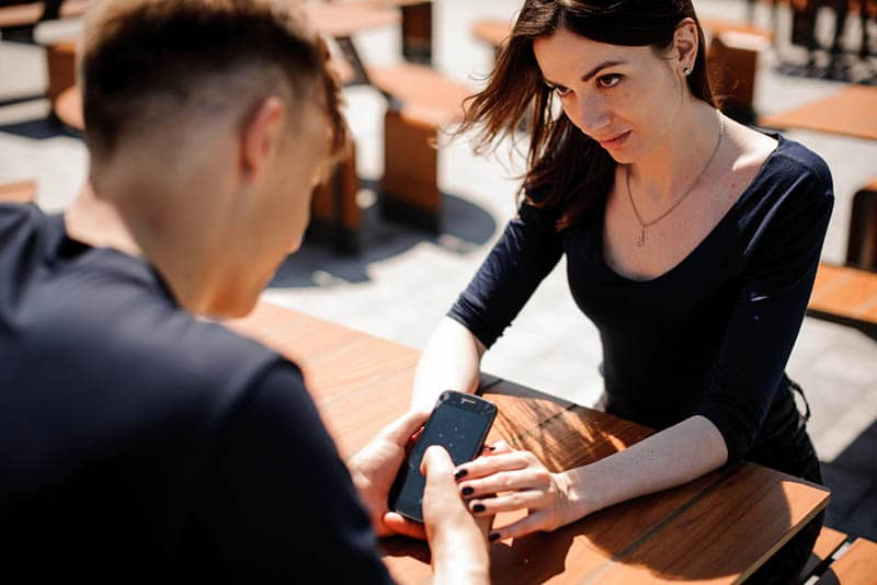 woman looking at man while holding his hand in street cafe