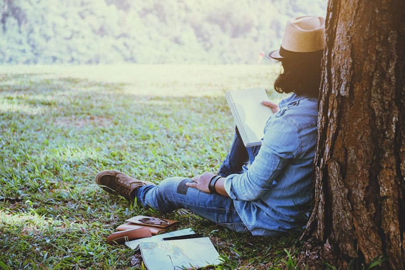woman reading book while leaning on tree
