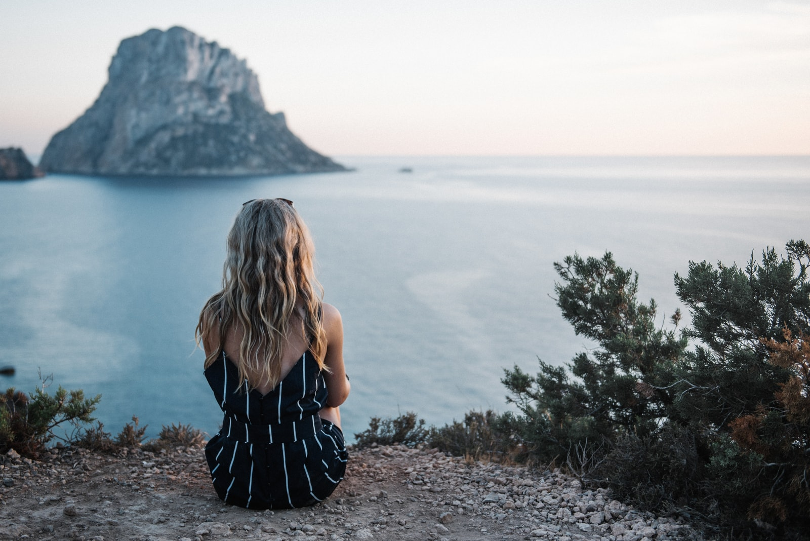 woman with long blond hair sitting by the sea alone