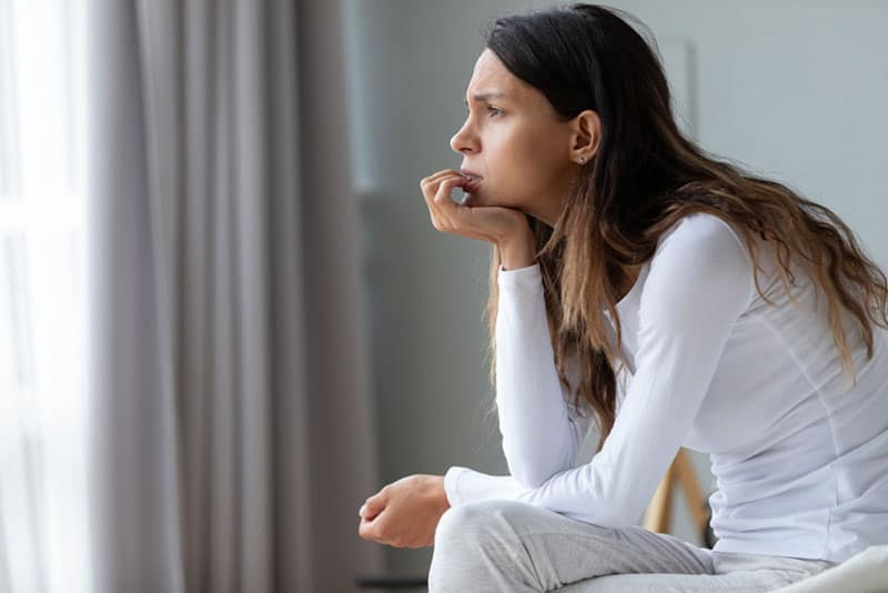 worried woman in deep thoughts sitting on the bed