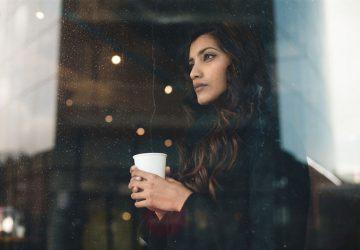 worried woman looking through the window